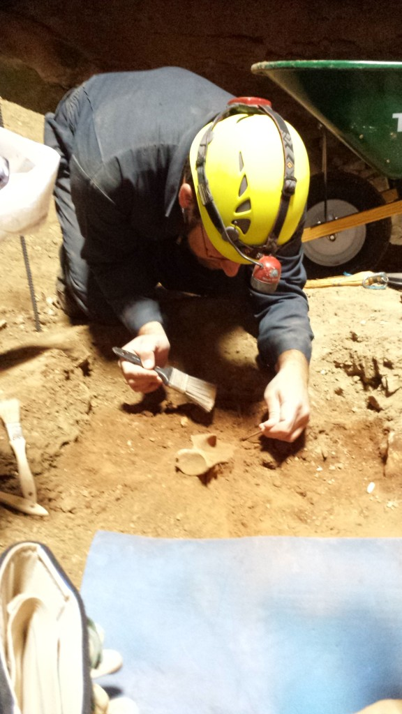 Postdoc Cory Redman uncovers a scapula (shoulder blade) that he uncovered.