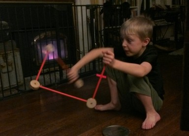 My son playing with Tinkertoys in front of thee fireplace.