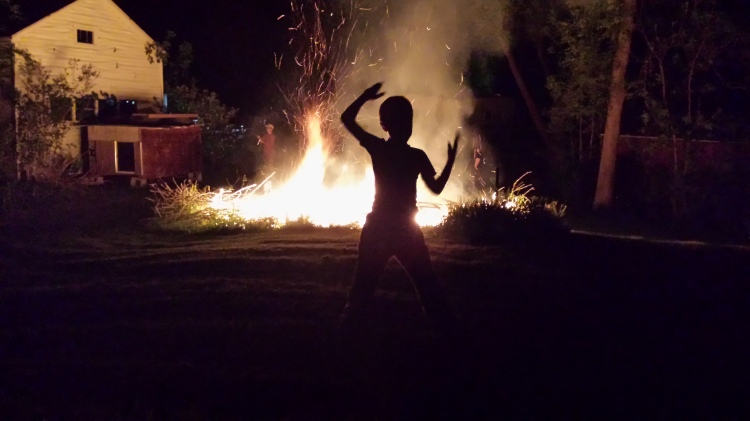 The boy jumps about in front of the blaze.