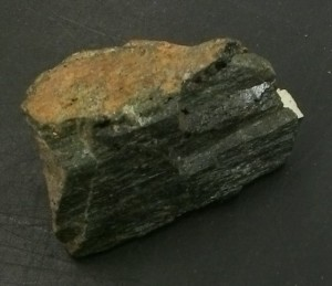 This mineral is part of the pyroxene group of minerals. It is called augite and looks a lot like hornblende.