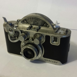 The arch on the top of the camera is to accommodate the rotary shutter.