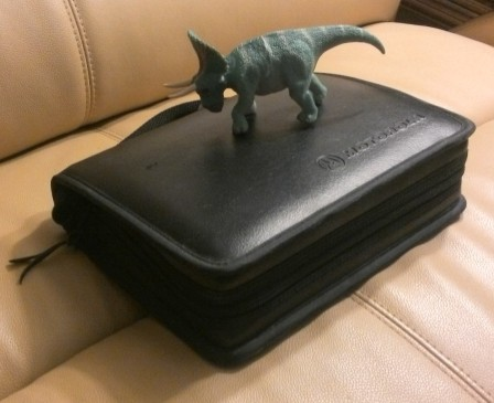 It zips all the way around, and has a handle on the top. Triceratops for scale.